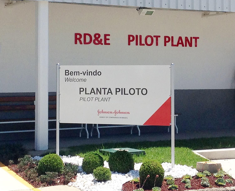 Placa de sinalização de fábrica em acrílico adesivada. Ao fundo letreiro em acrílico vermelho.